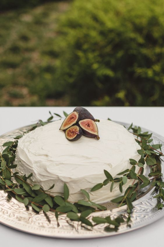 rock a gorgeous white textural wedding cake with greenery and fresh figs on top