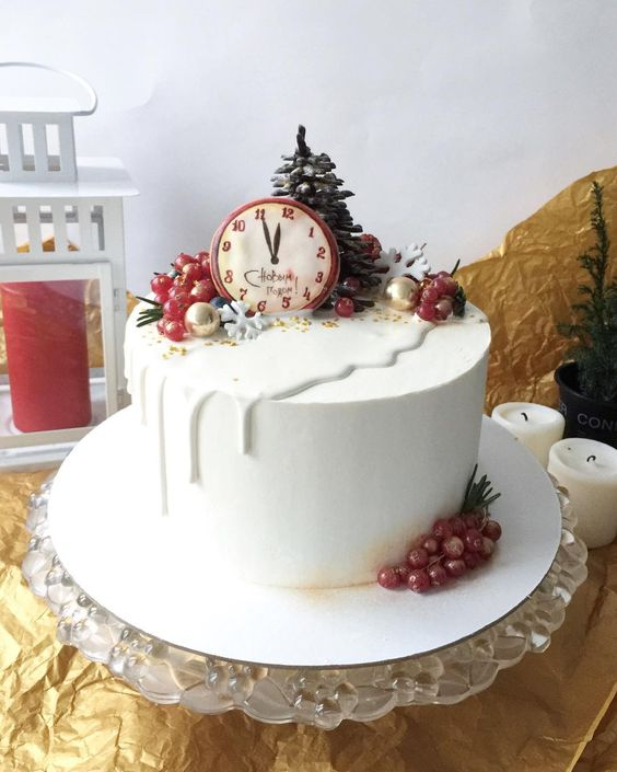a NYE wedding cake in white, with white chocolate drip, gilded berries, a mini fit tree and an edible clock is very whimsy