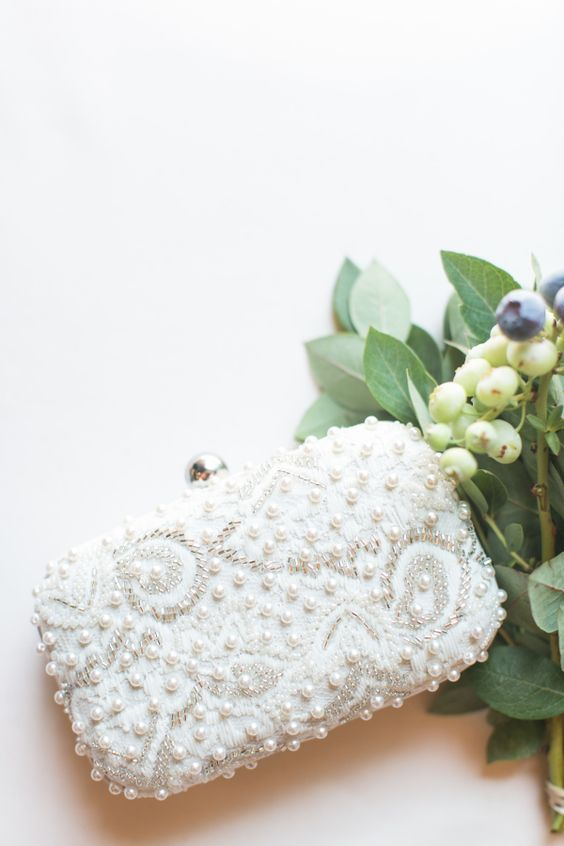 a beautiful pearly and bead embroidered clutch is classics for a modern glam bride