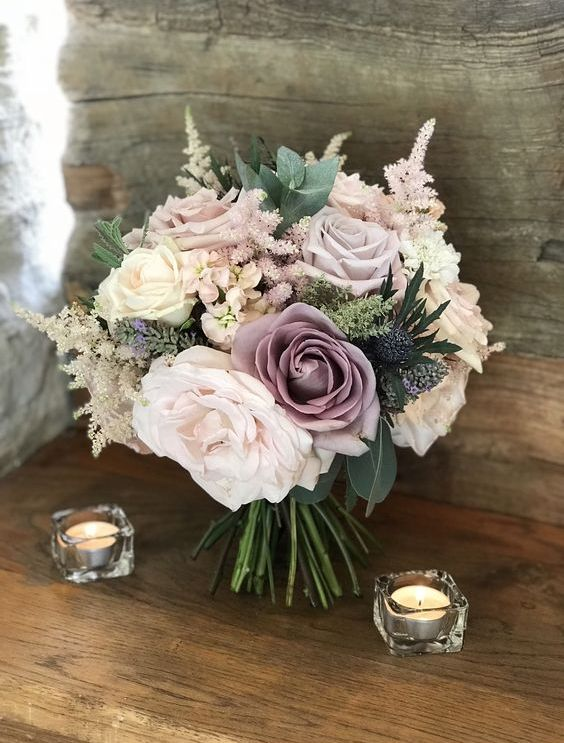 a beautiful wedding bouquet in muted tones - blush, mauve, ivory and with greenery