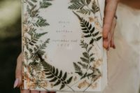 a beautiful wedding guest book decorated with gilded and dried foliage and herb for a rustic fall wedding