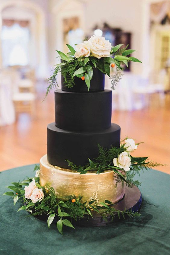 a black and gold wedding cake topped with greenery and blush blooms