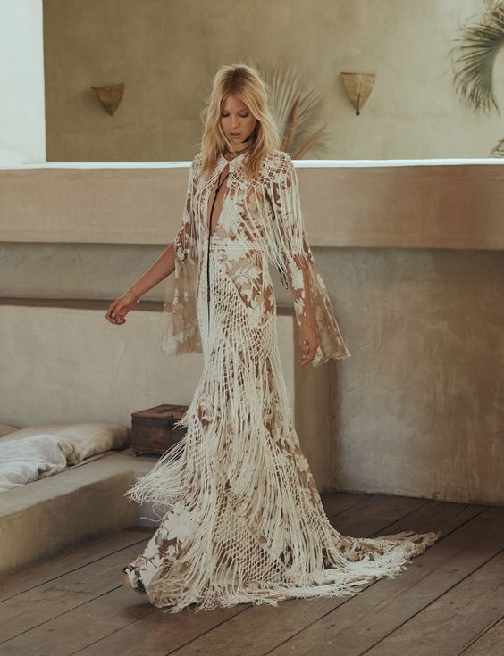 a boho nude lace A line wedding dress with a deep plunging neckline, bell sleeves and long fringe