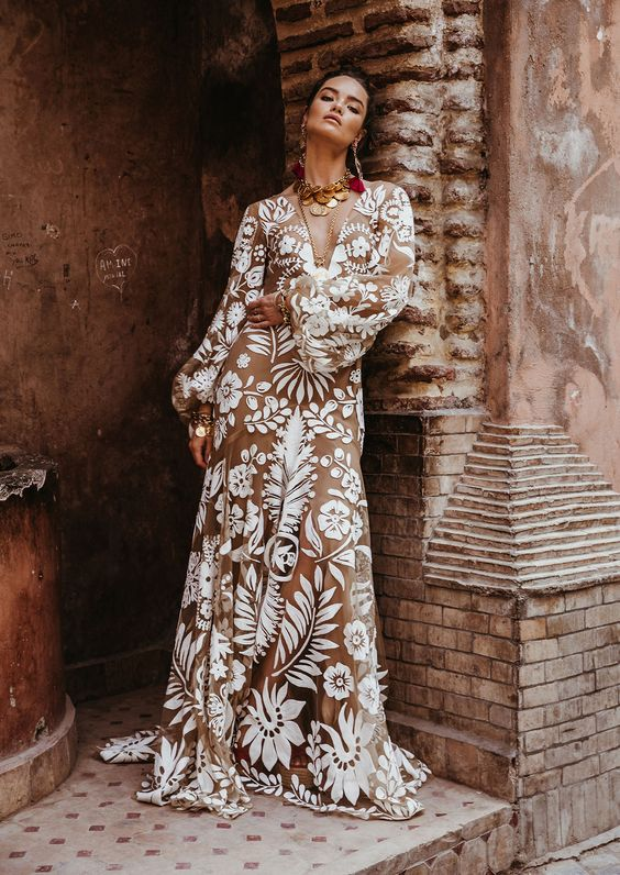 a bold boho nude lace wedding dress with a plunging neckline, long sleeves and a train plus statement accessories