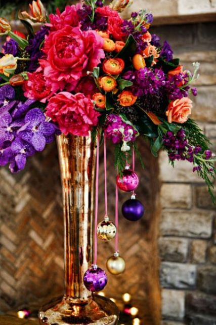 a bold winter wedding centerpiece in sumptuous colors and with bright ornaments hanging down from the vase