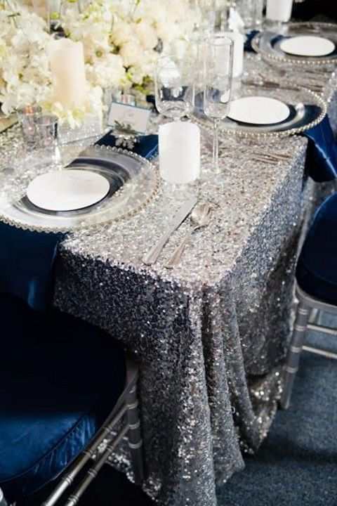 a bright wedding tablescape with a silver sequin tablecloth, navy chairs and napkins, candles and white blooms