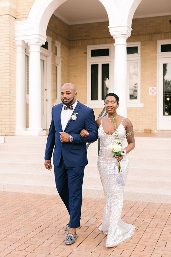 a chic couple with the groom in a navy suit and blue loafers and the bride in a white and silver sequin wedding dress looks very elegant
