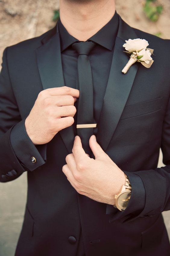 a chic groom's look with gold accents and a white and gold boutonniere