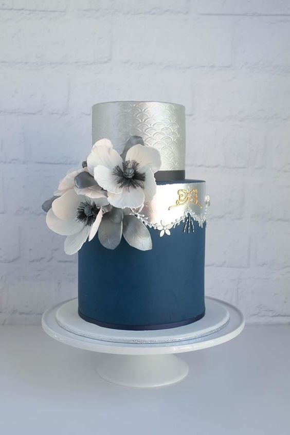 a chic navy and silver wedding cake with sugar blooms and ribbons plus some patterns