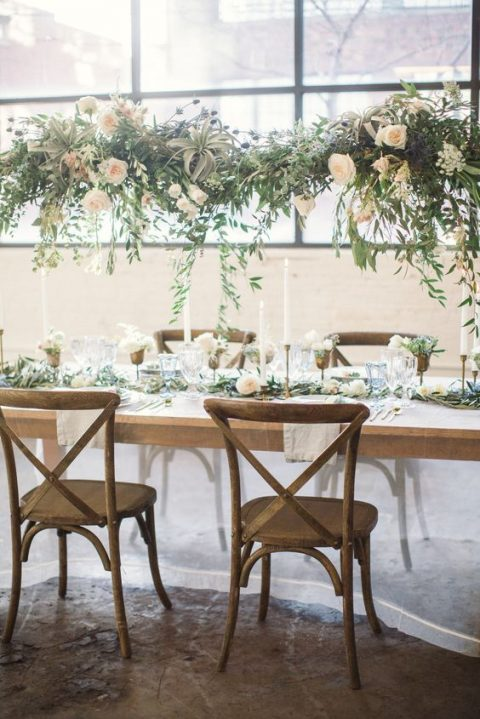 a chic overhead decoration of greenery, air plants and neutral roses and a matching runner