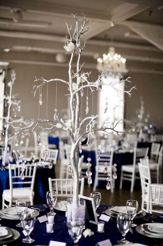 a chic wedding table with a navy tablecloth, a silver tree with crystals and white blooms plus candles