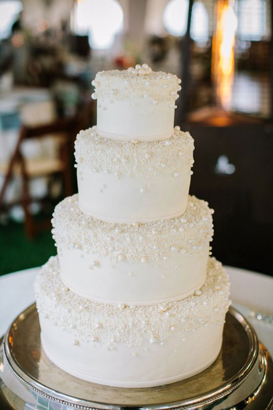 a chic white wedding cake covered with edible pearls is ultimate elegance that works for most of weddings