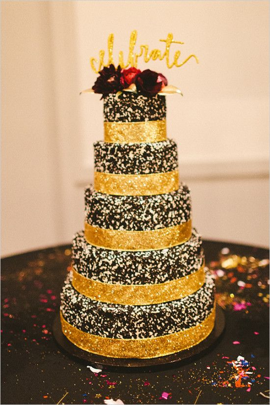 a chocolate wedding cake with glitter ribbons and dark blooms and a gold glitter calligraphy topper is very glam and chic
