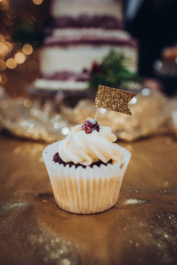 a cupcake topped with a raspberry and a gold gltiter flag topper is a lovely wedding dessert to enjoy