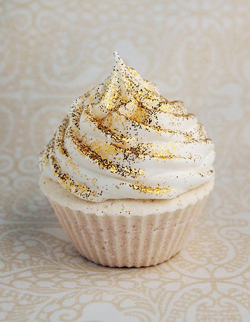 a cupcake with gold glitter on top is a lovely glam idea to rock at a NYE wedding and it will bring some fun