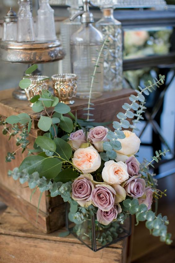a dimensional wedding centerpiece of eucalyptus, blusha dn mauve blooms and a clear vase