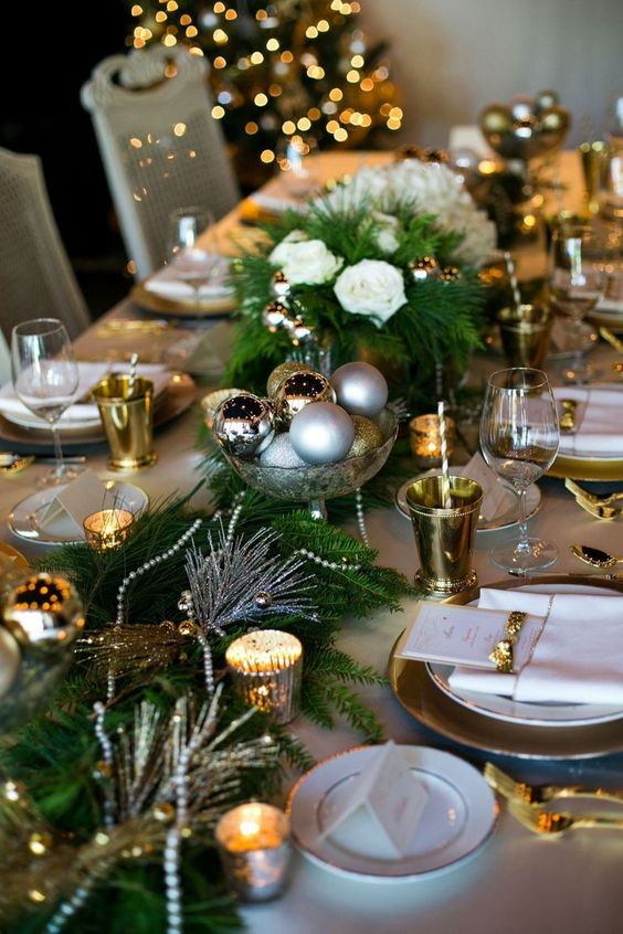 a festive table runner with evergreens, candles, beads and Christmas ornaments in a metallic bowl