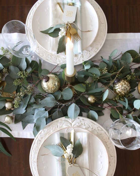 a festive table runner with frsh greenery and gold ornaments plus tall candles make the tablescape chic