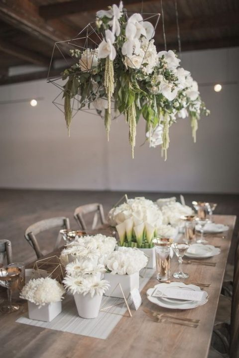 a geometric overhead wedding decoration of white blooms and much greenery