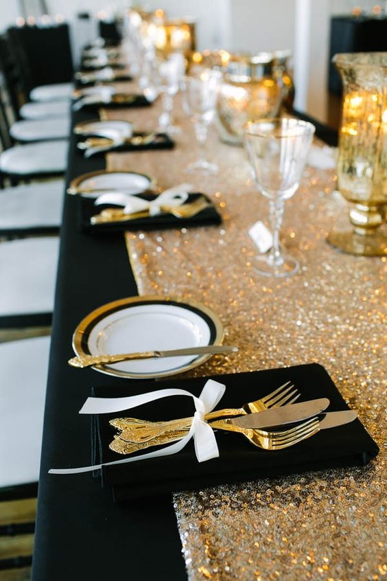 a glam black and gold wedding tablescape with a sequin runner, striped plates and a black velvet napkin