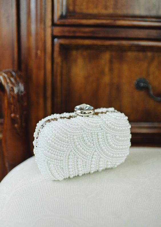 a glam pearl clad clutch with a large rhinestone on top is a chic statement piece for a bride
