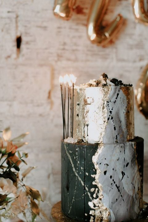 a gorgeous black, silver and gold leaf wedding cake with tall and thin candles for decor