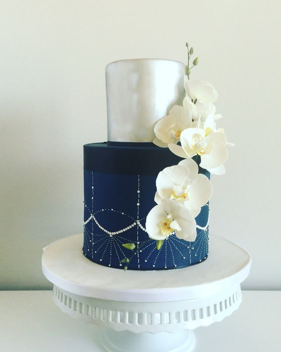 a gorgeous navy and silver wedding cake with embellishments and white sugar orchids is a stunning idea for a modern glam wedding