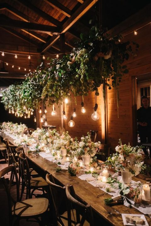 a greenery overhead wedding decoration with bulbs hanging down brings an outdoor feel to the space