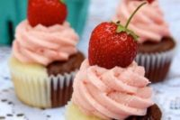 a half vanilla and half chocolate cupcake with strawberry frosting and a fresh strawberry is a gorgeous combo