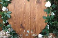a heart-shaped plywood sign with the wedding date and monograms lined up with fresh greenery and white blooms