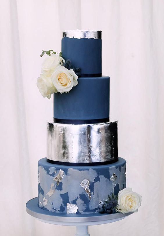 a large navy and silver foil wedding cake with various tiers and fresh blooms