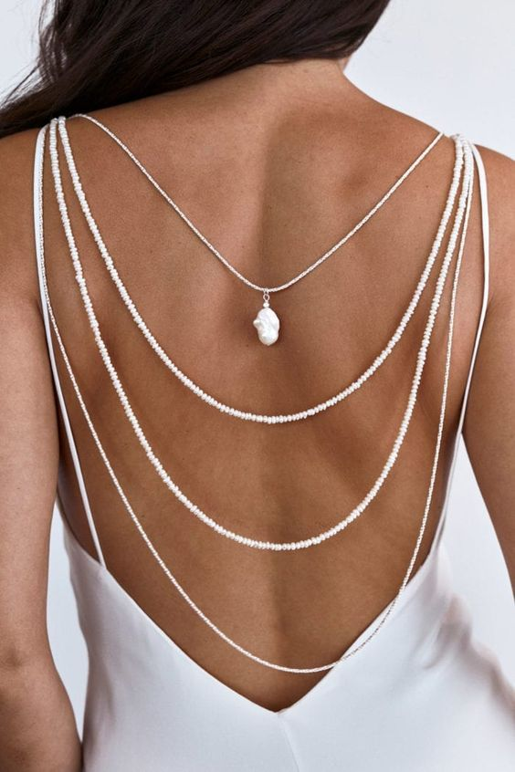 a layered back necklace of small pearls plus a large baroque one to highlight the open back of the wedding dress