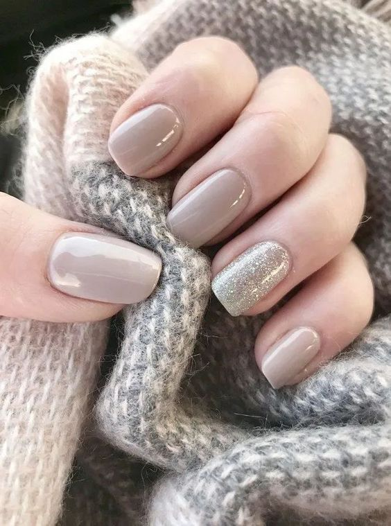 a light grey manicure and a silver glitter accent nail compose a stylish glam manicure for a winter bride