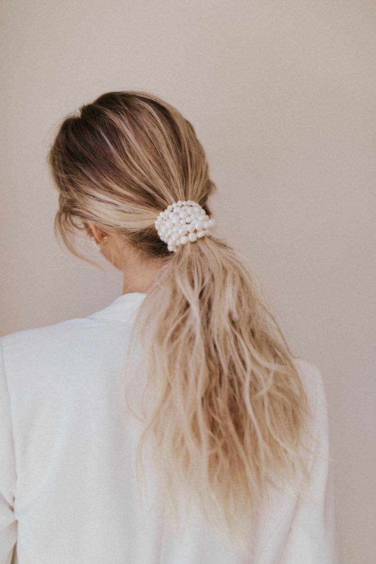 a low and messy ponytail wrapped up in pearls is a chic idea for a modern or minimalist bride