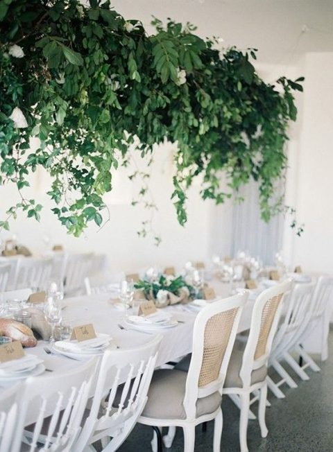 a lush cascading greenery wedding decoration with some white blooms