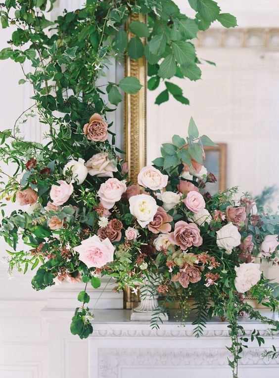 a lush dimensional wedding centerpiece with blush, mauve and white blooms and textural greenery