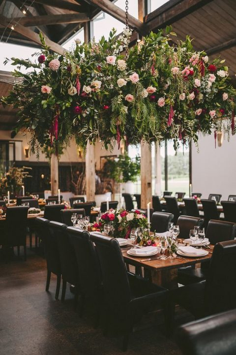 a lush greenery and floral overhead wedding decoration and matching centerpieces