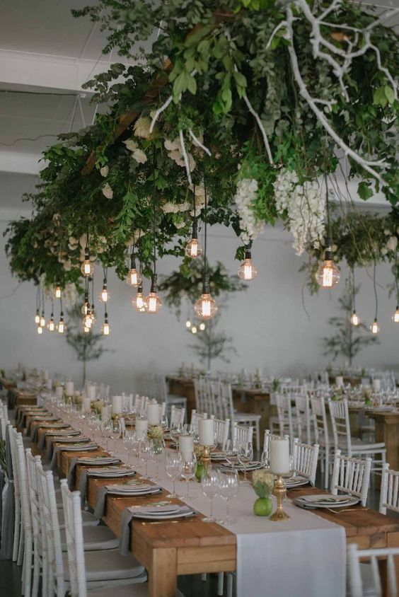 a lush greenery and white bloom installation with bulbs hanging down is a bold modern decor idea