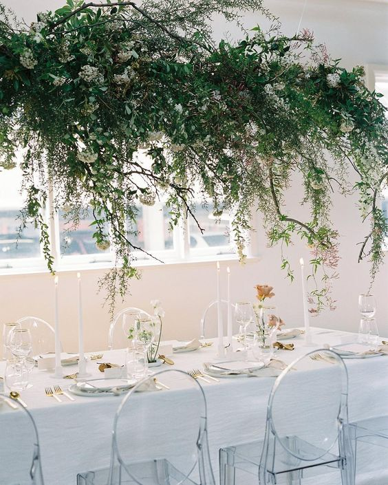a lush greenery and white bloom wedding installation over the reception table for a refreshing spring feel
