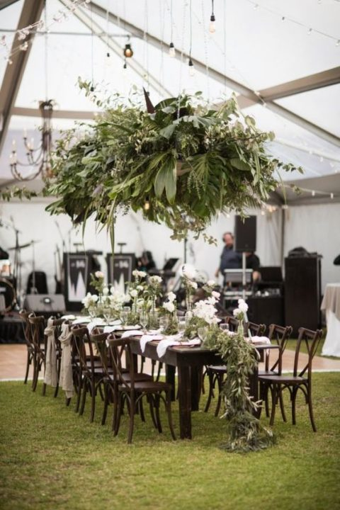 a lush greenery overhead decoration with all kinds of leaves and a matching greenery runner