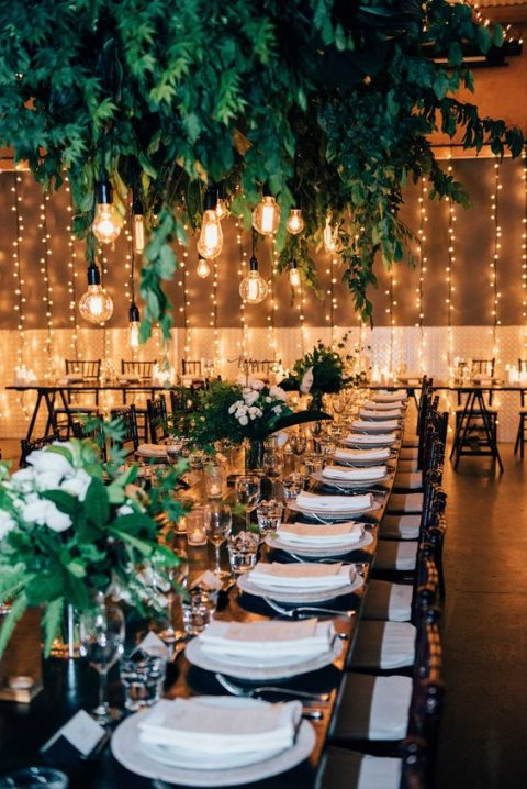 a lush greenery overhead decoration with bulbs hanging down for a cozy ambience