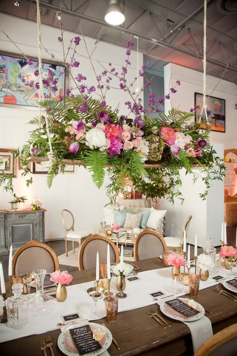 a lush overhead floral decorations with ferns and colorful blooms