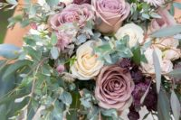 a lush textural wedding bouquet with greenery, mauve, purple and ivory blooms