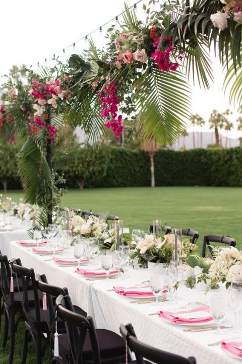 a lush tropical overhead wedding decoration with pink and blush blooms and tropical leaves