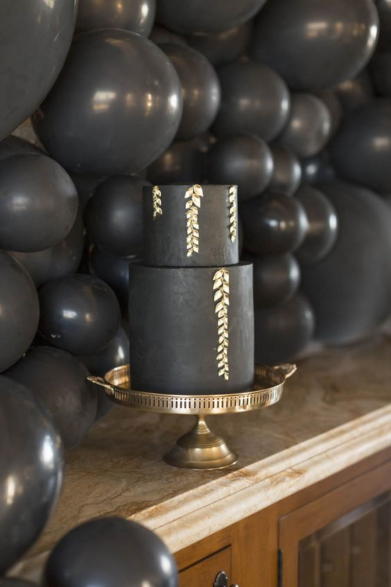 a matte black wedding cake decorated with gold patterns looks very chic and refined