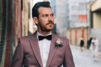 a mauve groom's suit with a white shirt and a burgundy velvet bow tie for a unique look