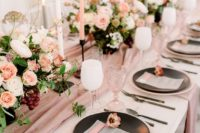 a mauve table runner and napkins plus blush and white blooms plus candle to make up a chic and refined look