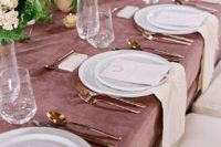a mauve tablecloth, blush and yellow blooms and copper cutlery for a refined and delicate tablescape