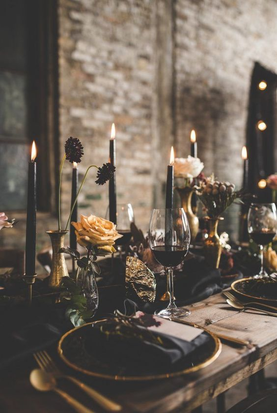 a moody wedding tablescape with black candles, black and gold chargers and a black runner and gold cutlery