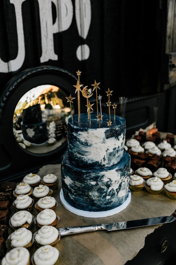 a navy and white marble wedding cake with star and moon toppers is a fun and bold idea with a touch of glam